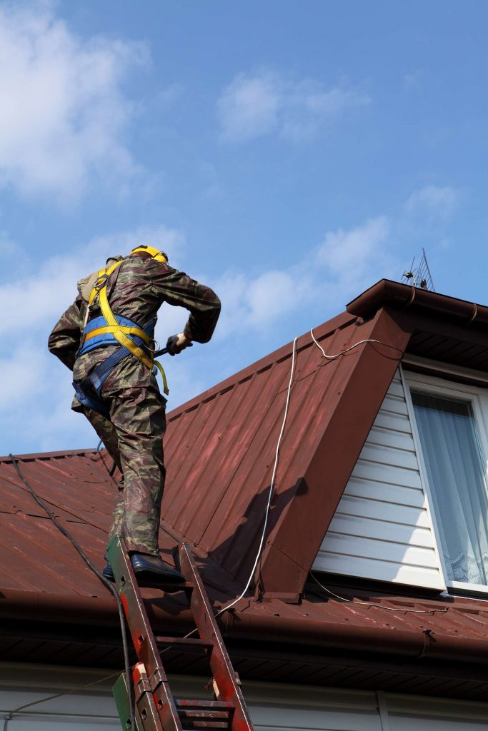 roofer wearing a safety harness on construct site