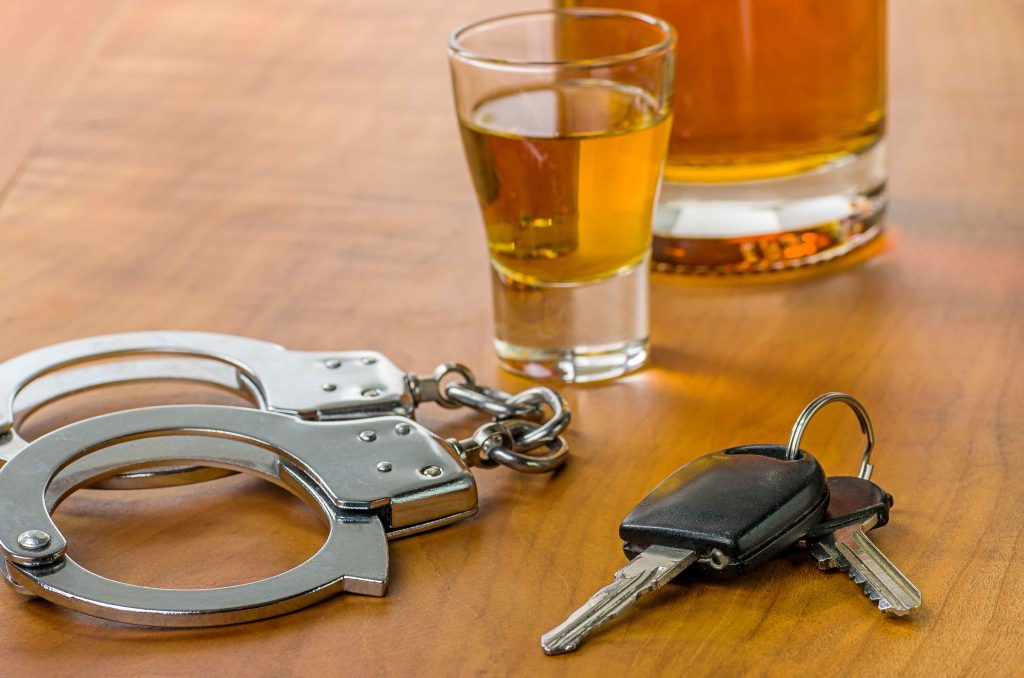 Keys and cuffs with liquor glass at bar equals arrest